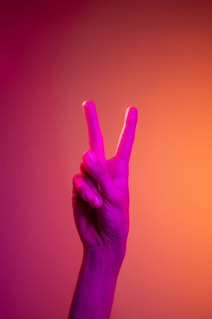 person doing peace sign hand gesture