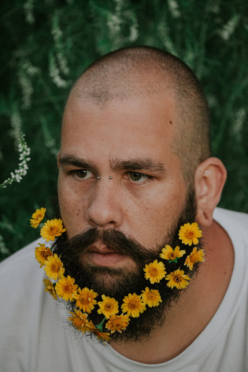 thoughtful man with beard decorated with gentle flowers